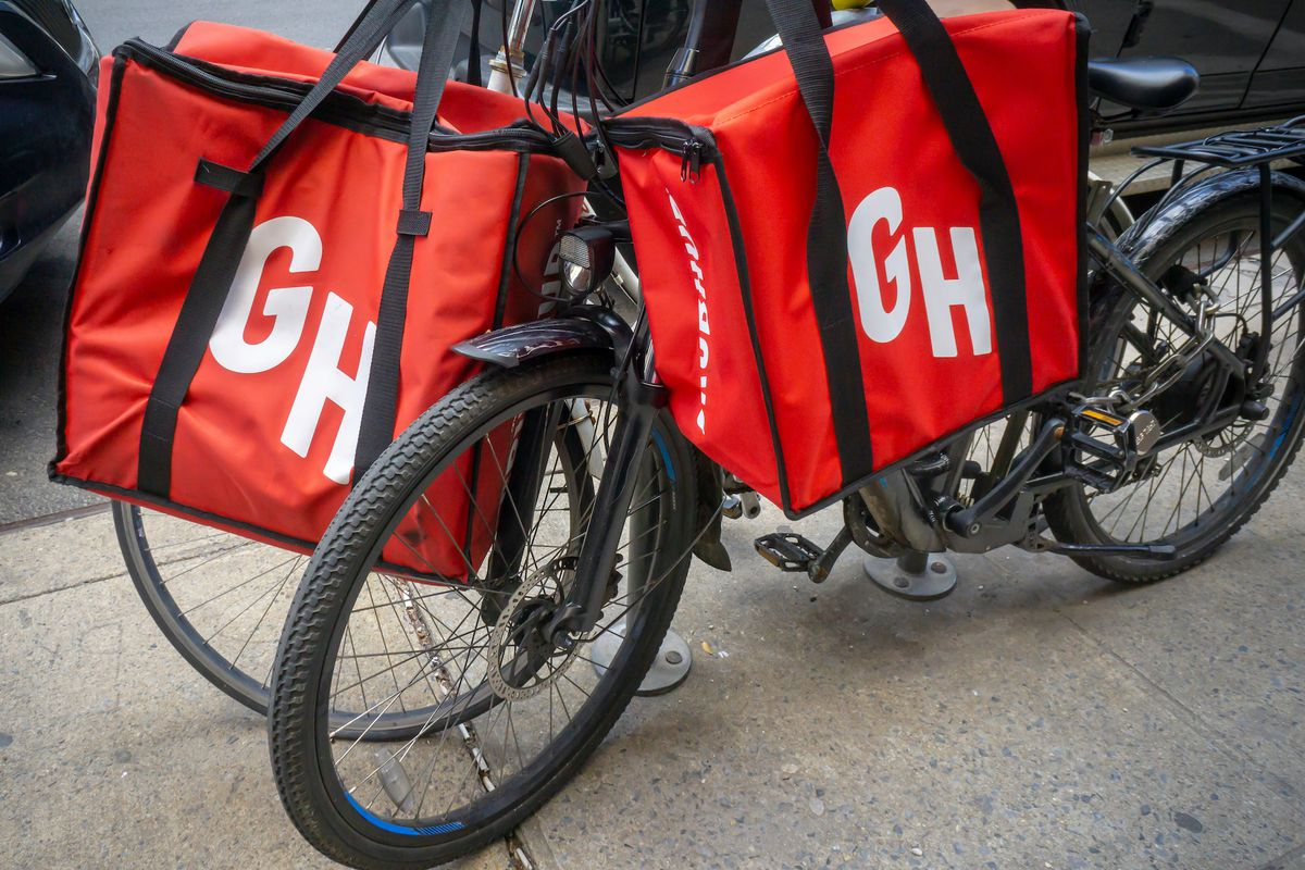 A bike parked on the side of the street that holds to delivery bags that are red and have the letters G and H printed on them.