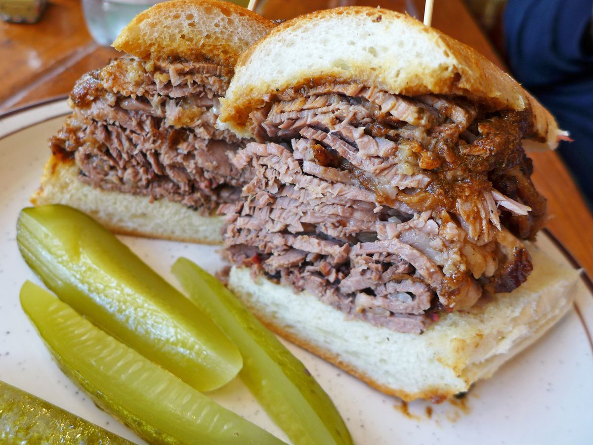 Two halves of a brisket sandwich on a club roll with gravy, accompanied by four pickle spears