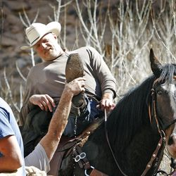 """Former 7'4"""" Utah Jazz center Mark Eaton  drains the water out of his boots after being drenched in the San Rafael River after hitting a deep hole while while riding horses down the Little Grand Canyon of the San Rafael Swell  Saturday, April 2, 2011, in the San Rafael Swell in Central Utah."""