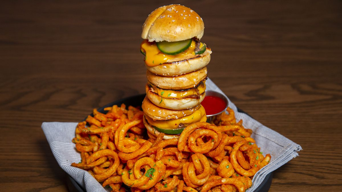 A pile of burgesr on a bed of curly fries