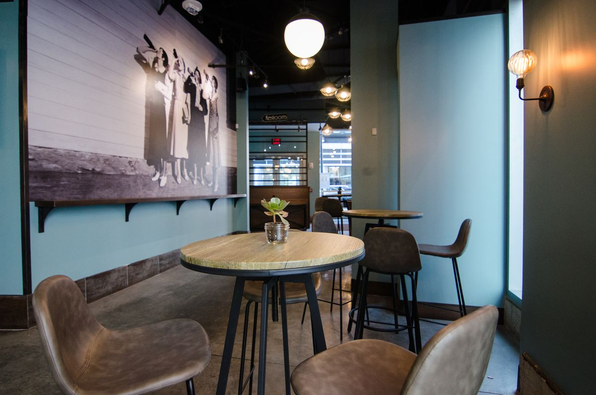 Several high-top tables in the lounge area of a restaurant. The walls are light blue, and an old black-and-white photograph of four women in dresses, drinking booze from bottles, covers most of one wall.