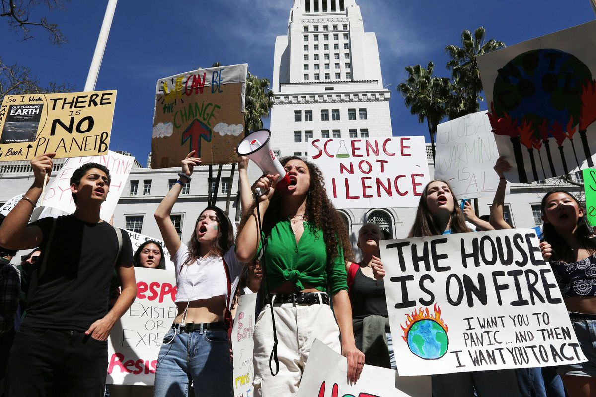 "Climate activists at a rally shout into a megaphone and carry signs reading, ""The house is on fire,"" and, ""Science not silence."""