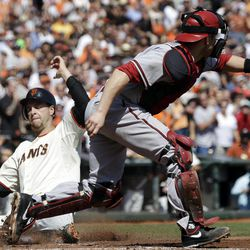 San Francisco Giants' Brandon Belt, left, scores on a double by Hector Sanchez as Arizona Diamondbacks catcher Miguel Montero, right, waits for the throw during the second inning of a baseball game, Thursday, Sept. 27, 2012, in San Francisco.