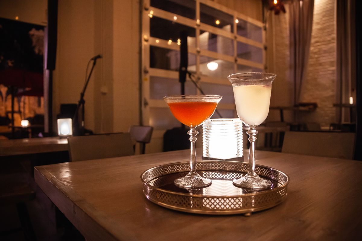 A bright red Hanky Panky cocktail in a coup glass next to a milky colored Bees Knees cocktail in a vintage wine glass on a silver tray, a closed garage door in the background