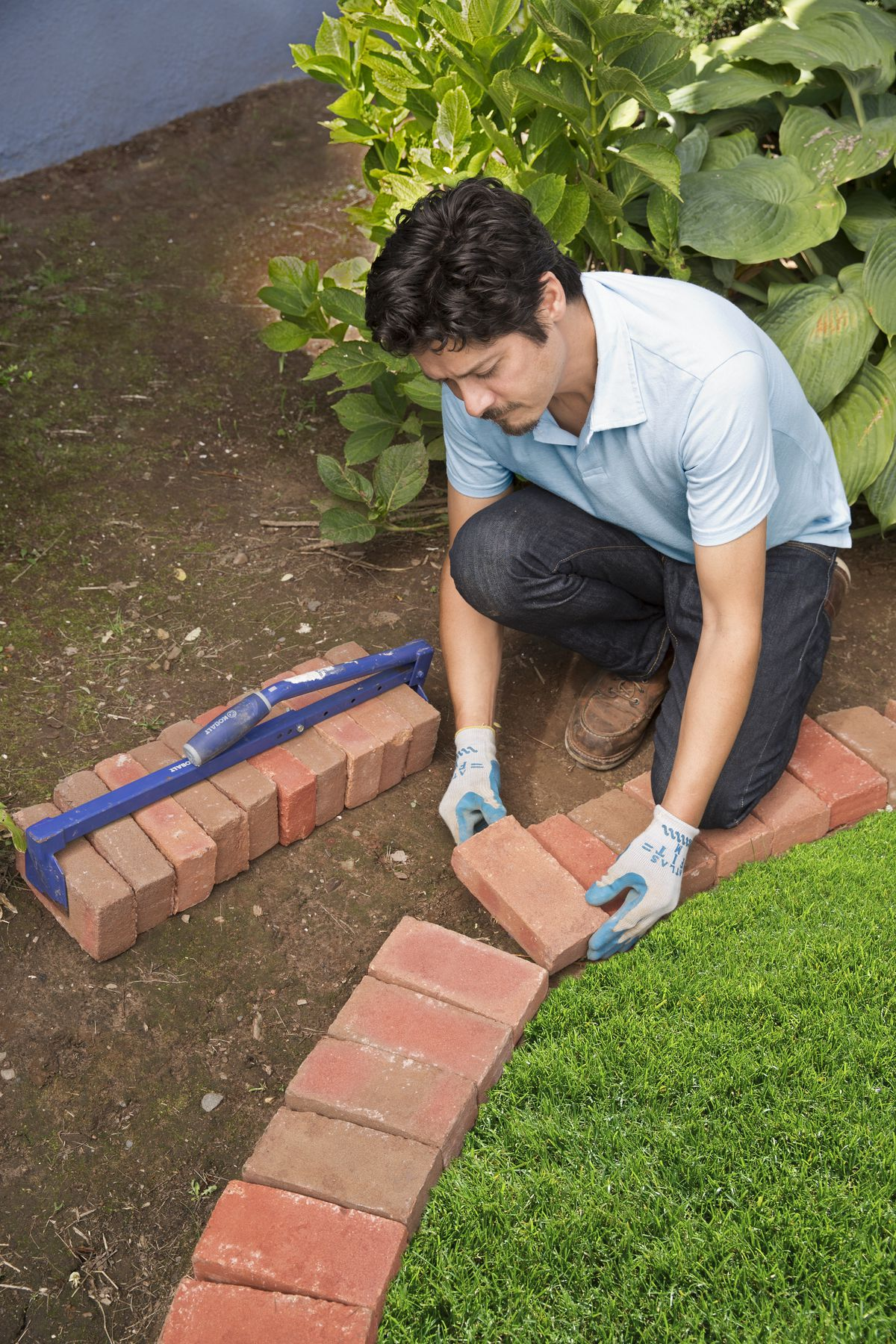 Man Edges Bed With Bricks Against Grass Line