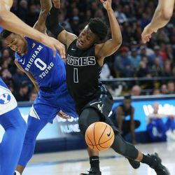 Utah State Aggies guard Koby McEwen (1) and Brigham Young Cougars guard Jahshire Hardnett (0)  get tangled up in Logan on Saturday, Dec. 2, 2017. BYU won 75-66.