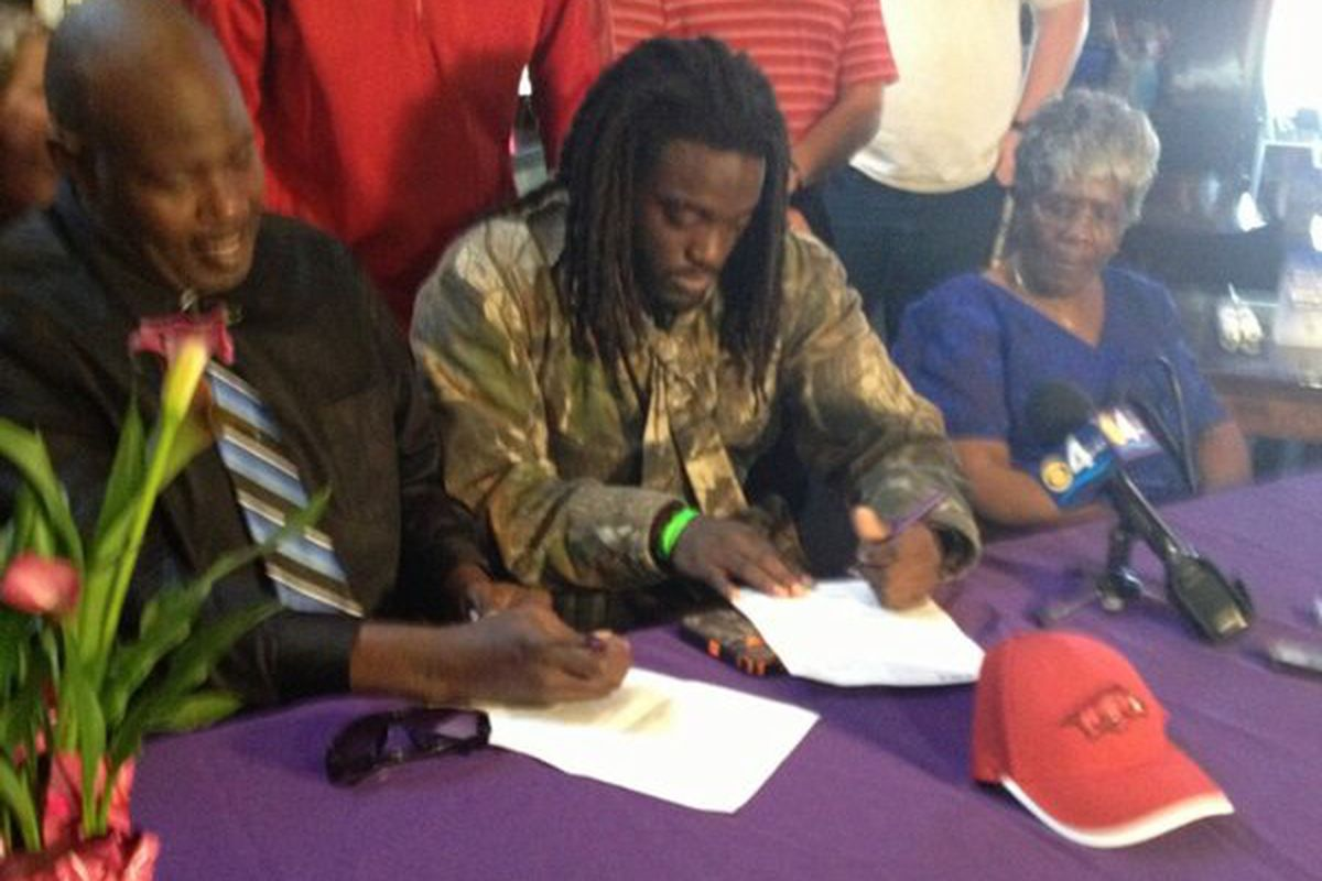 Alex Collins, wearing his best head-to-toe camo, finally signs his Arkansas LOI