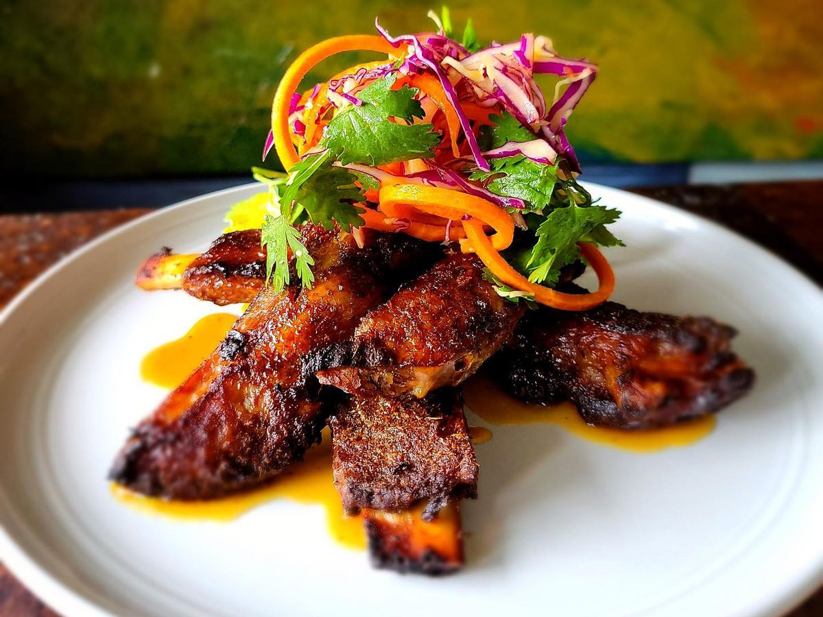 Ribs plated elegantly with a carrot radicchio slaw on top