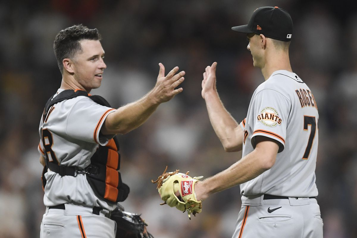 Donovan Solano #7 of the San Francisco Giants is congratulated by Buster Posey #28 after getting the final out during the ninth inning of a baseball game against the San Diego Padres at Petco Park on September 21, 2021 in San Diego, California. The Giants won 6-5.