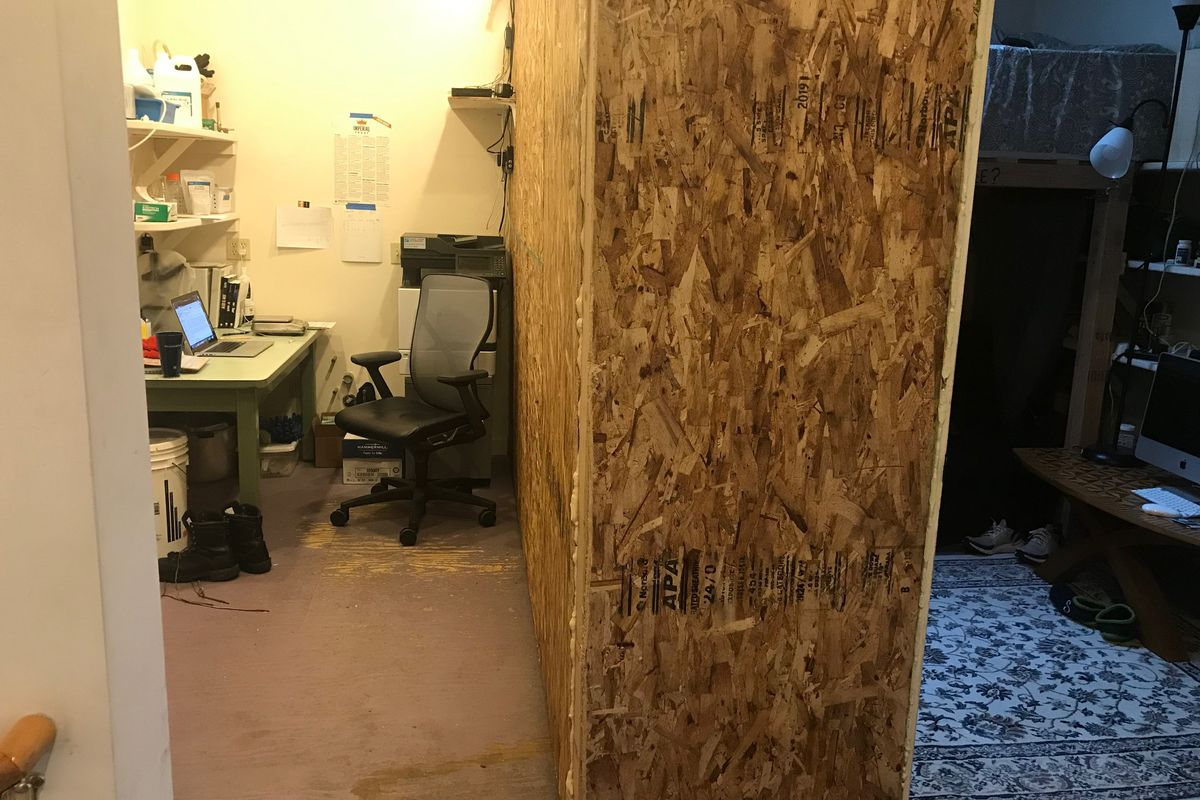 A small bedroom and office separated by a wooden, corkboard barrier