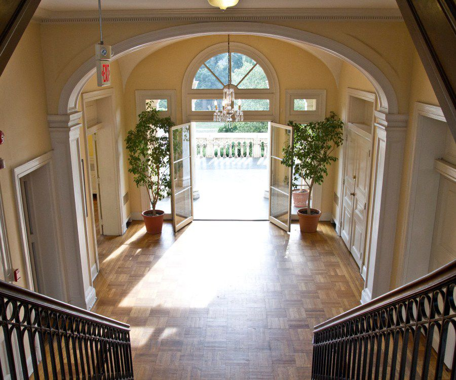 The interior of the Josephine Butler Parks Center in Washington D.C. There is a staircase and an arched door that has two plants on either side of it.