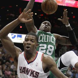 Boston Celtics' Mickael Pietrus, rear, grabs a rebound away from Atlanta Hawks' Joe Johnson during the second quarter of Game 1 of an opening-round NBA basketball playoff series, Sunday, April 29, 2012, in Atlanta.