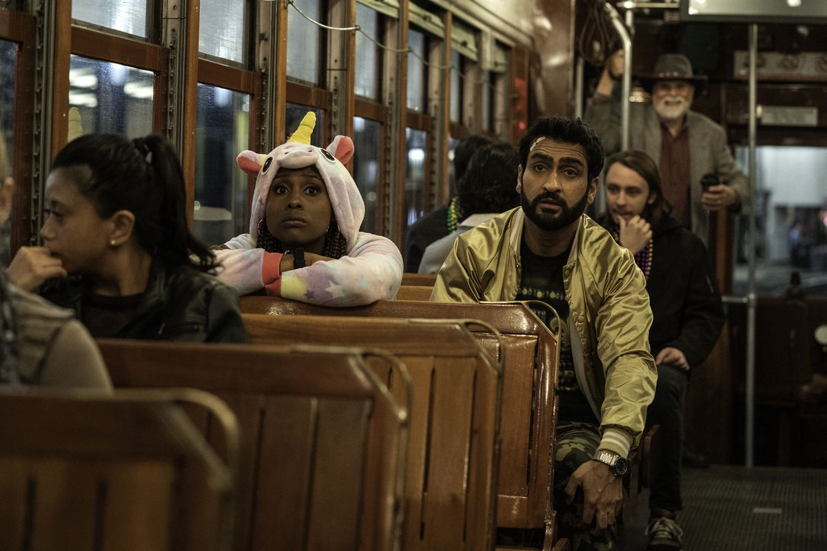 issa rae in a unicorn onesie and kumail nanjiani in a gold bomber jacket