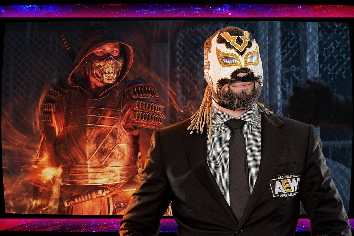 Man wearing a suit and wrestling mask stands in front of an image from the Mortal Kombat movie.