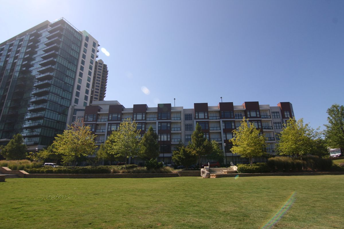 A low-rise apartment building next to a taller tower with a green lawn in the foreground.