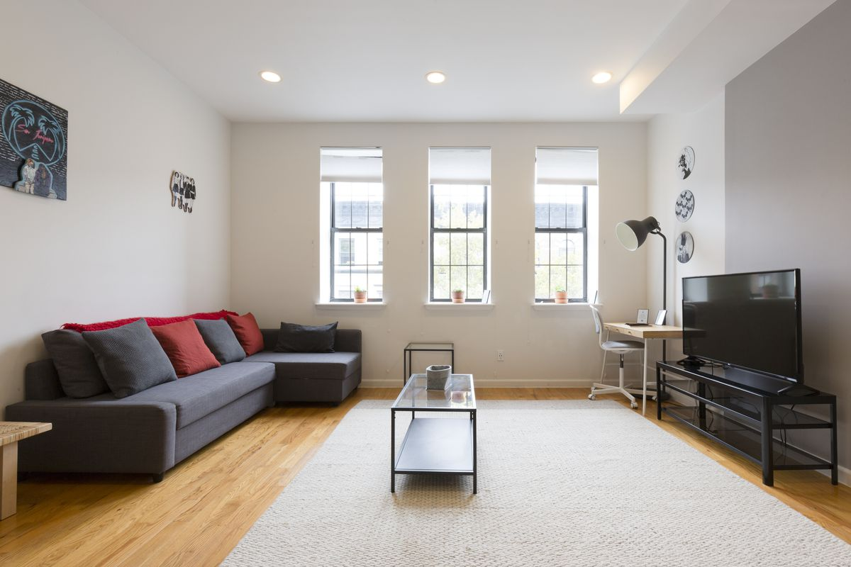 A living area with hardwood floors, three windows, a dark grey couch, a small coffee table, and a beige rug.