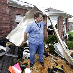 """Randy McKeever, removes part of what he believes is his neighbors garage door from the front of his tornado damaged home Wednesday, April 4, 2012, in Forney, Texas. The mayor of Forney, Texas, says it's """"a real blessing"""" that nobody was killed in the community by the tornadoes that ripped through parts of the Dallas area yesterday.  (AP Photo/Tony Gutierrez)"""