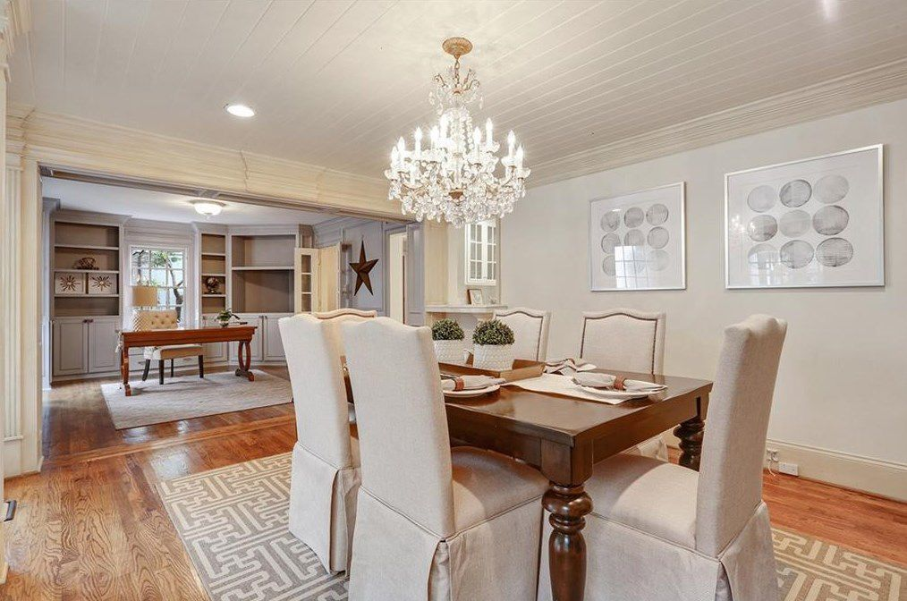 A white dining room with a big chandelier and an open office.
