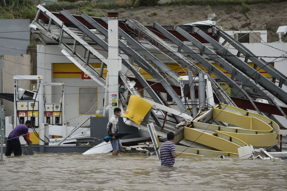 People walk next to a gas station flooded and damaged by Hurricane Maria, which hit the eastern region of the island, in Humacao, Puerto Rico, on Wednesday. The strongest hurricane to hit Puerto Rico in more than 80 years destroyed hundreds of homes, knoc