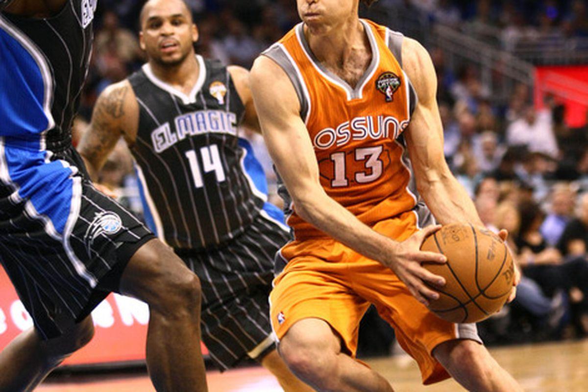 Mar 21, 2012; Orlando, FL, USA; Phoenix Suns point guard Steve Nash (13) drives around Orlando Magic center Dwight Howard (12) during the first quarter at Amway Center. Mandatory Credit: Douglas Jones-US PRESSWIRE