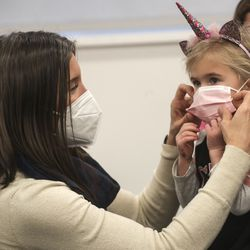 Salt Lake City Mayor Erin Mendenhall helps 3-year-old Della Barker Asman with her mask as she visits with preschool children at Neighborhood House in Salt Lake City on Tuesday, Dec. 22, 2020. Mendenhall was there to help distribute food via the Nourish to Flourish program.