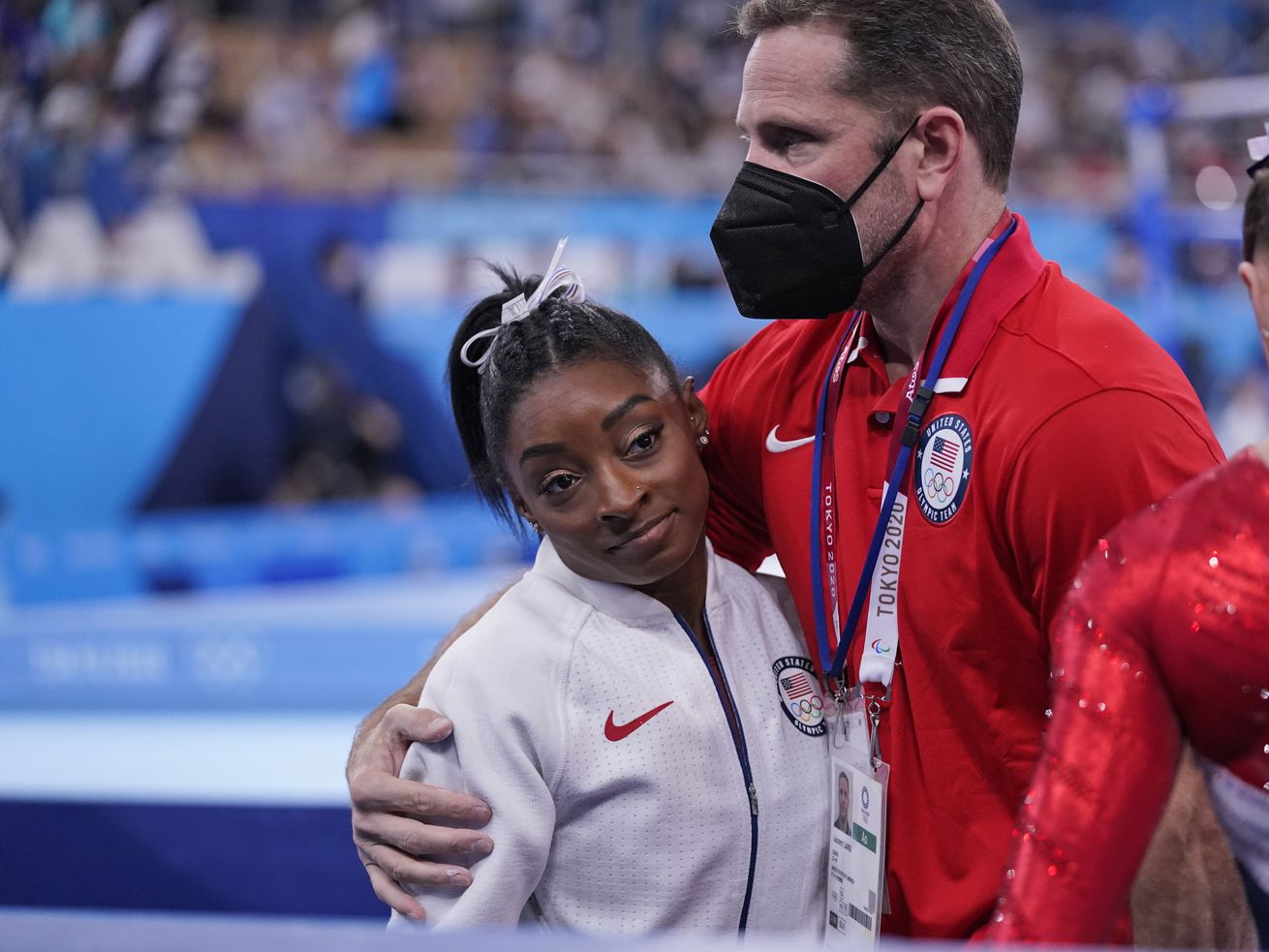 Coach Laurent Landi embraces Simone Biles after she exited the team final at the 2020 Summer Olympics on Tuesday, July 27, 2021, in Tokyo.