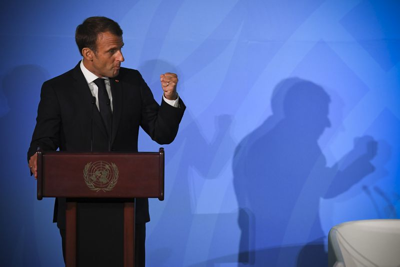 French President Emmanuel Macron onstage at the UN Climate Summit holds up his fist.