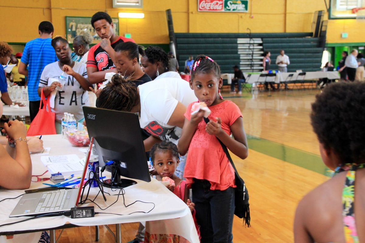 Children snack on donuts at a housing fair at Booker T. Washington High School in late July in an effort to relocate families from the Foote Homes.