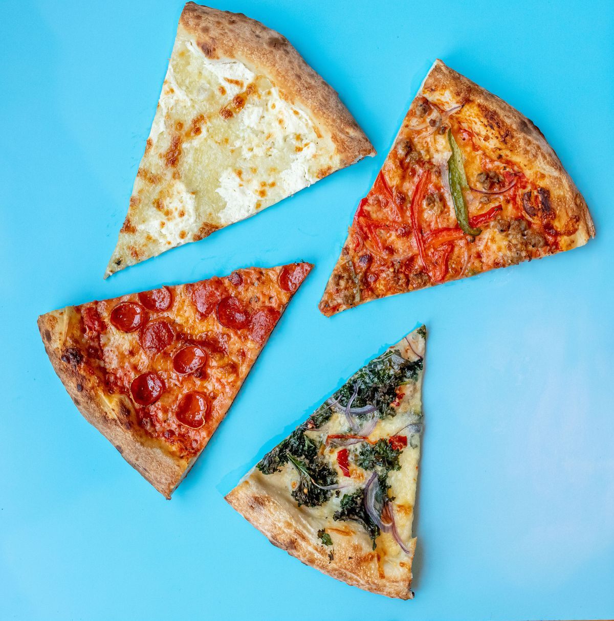 Four slices from Slice Joint, ranging from a white pizza to vegetable specials and pepperoni