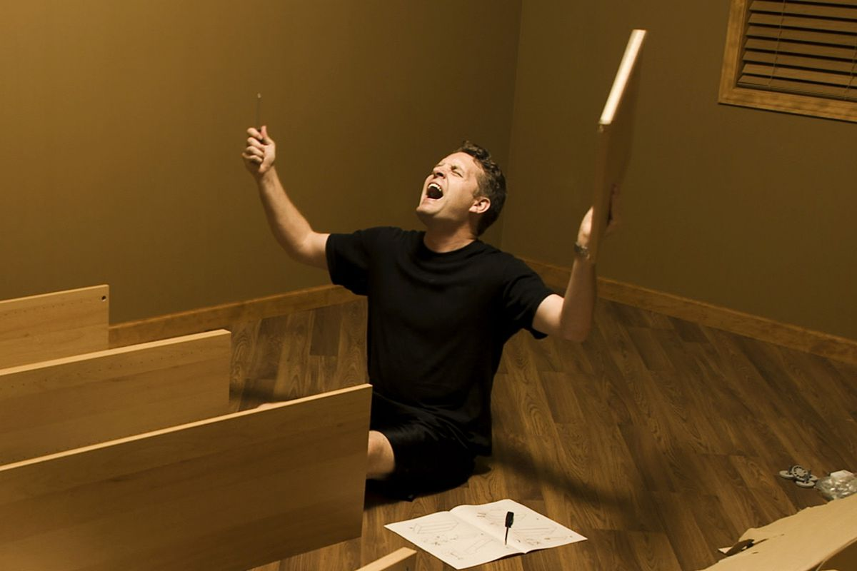 A man sitting on the floor building an Ikea bookcase raises his face and arms to the ceiling and yells.