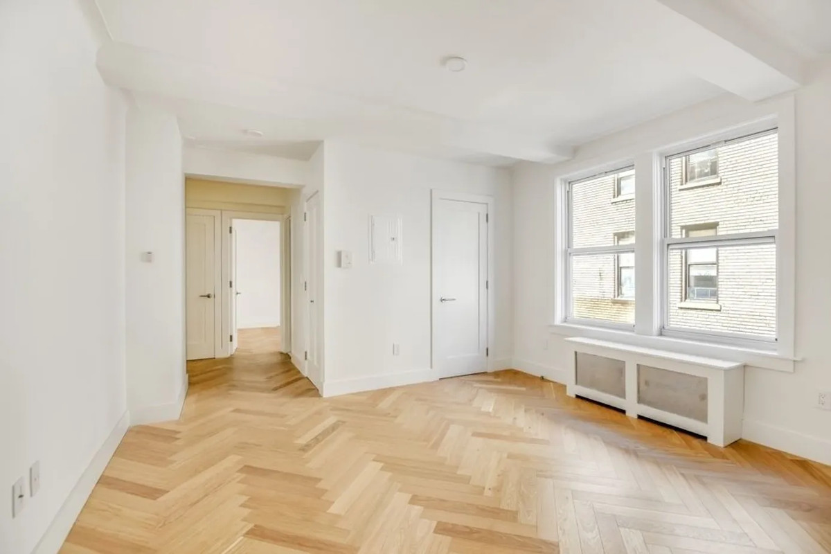 A bedroom with hardwood floors, large windows, and beige walls.