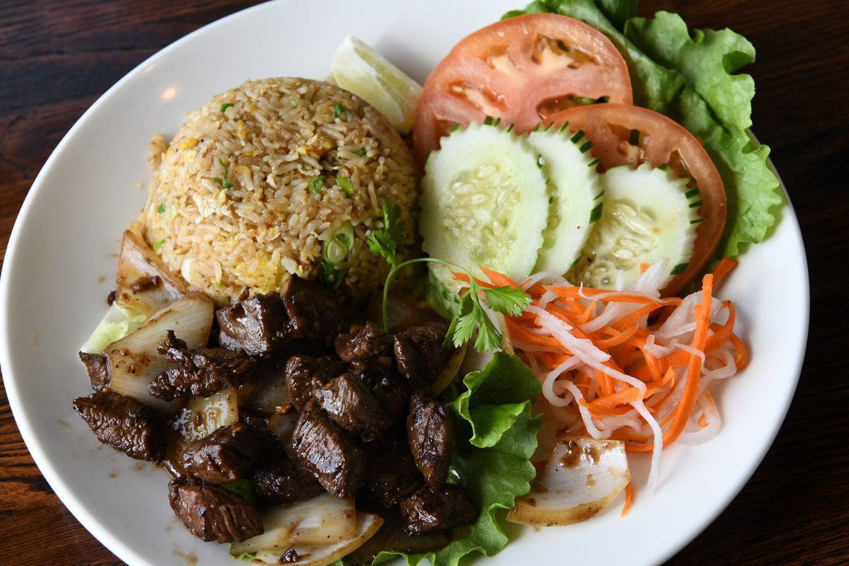 A plate with shaking beef, broken rice, tomatoes, cucumbers, and sliced pickled carrots
