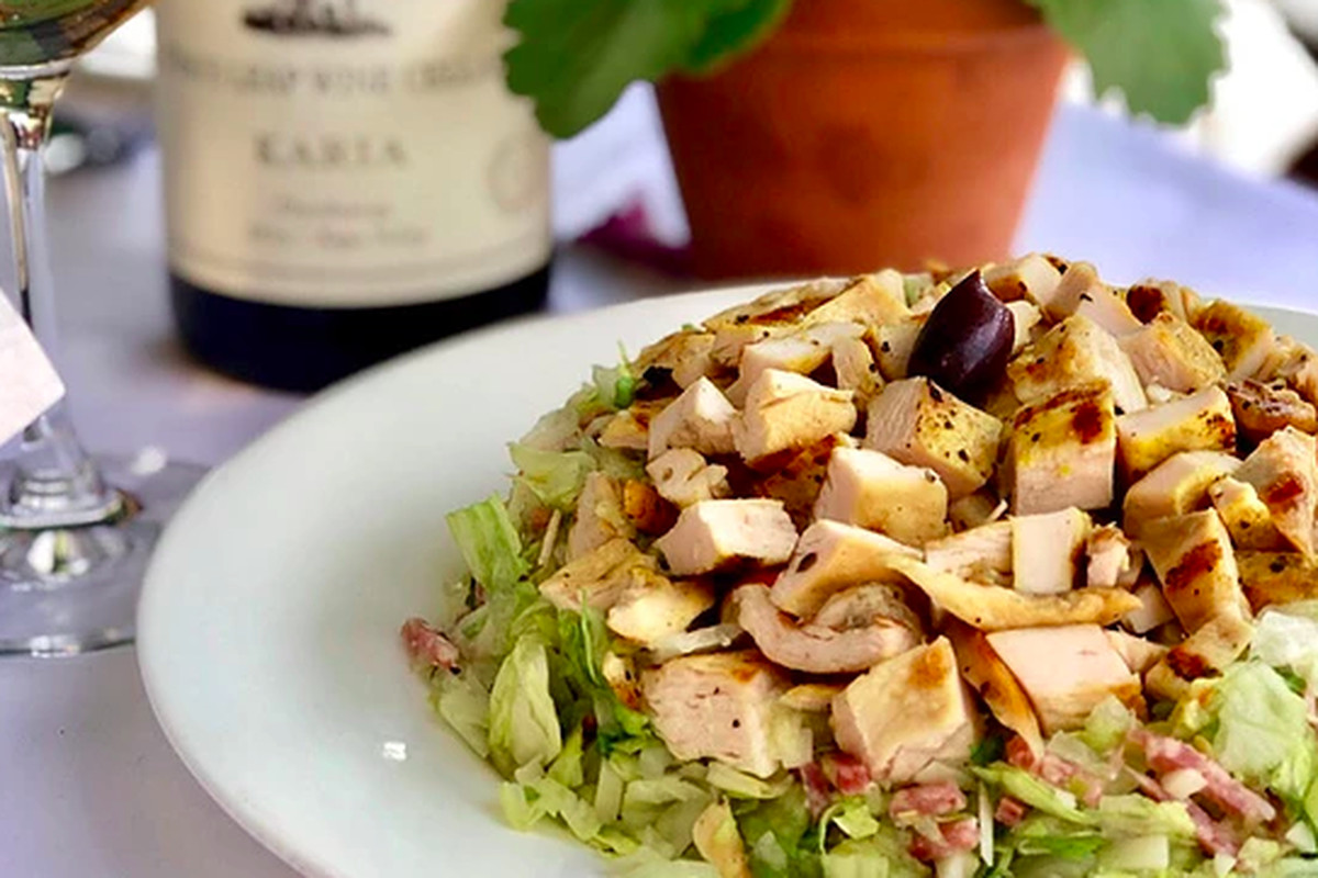 La Scala's chopped salad served in front of a bottle of wine.