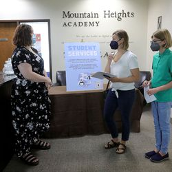 Jessica Curless, Mountain Heights Academy student services, directs Stasha Lewis and eighth grader Emma Lewis where to go next during in-person orientation at the online school based in West Jordan on Tuesday, Aug. 24, 2021.