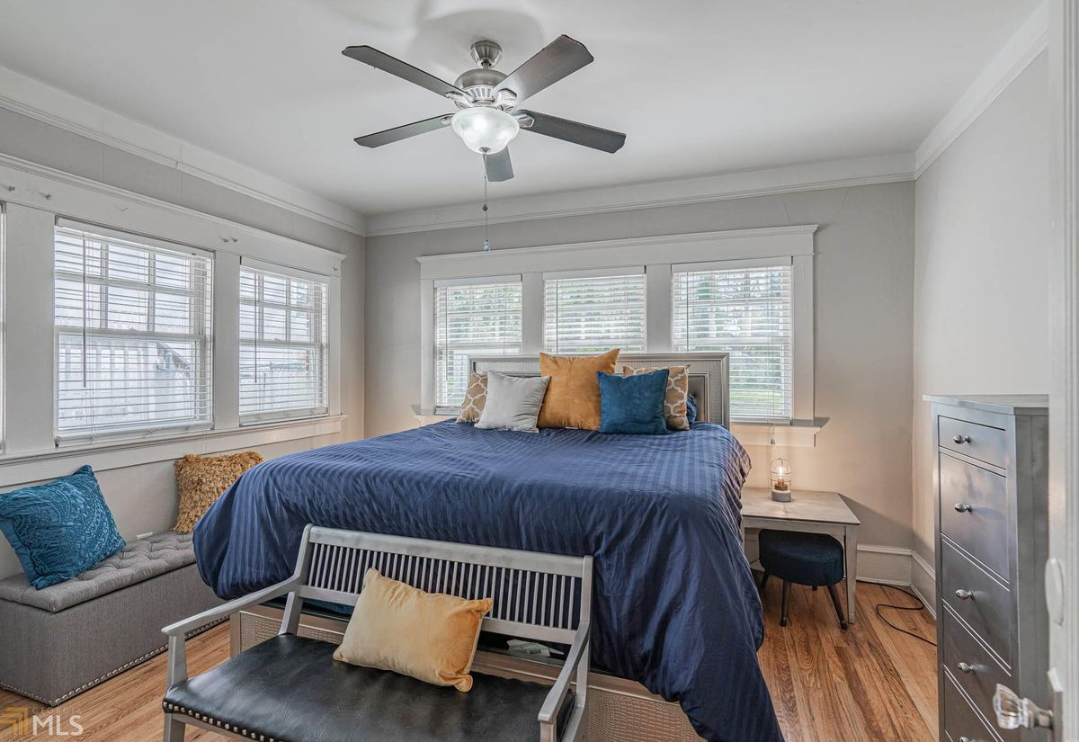 A white and gray bedroom with a ceiling fan overhead and blue blankets on the bed.