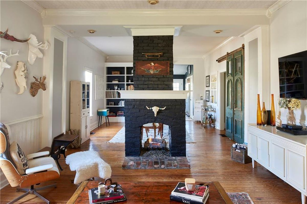 An interior with many skulls on the walls and a double-sided fireplace and an Eames chair.