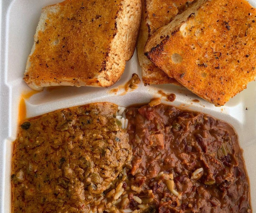 A subdivided takeout container with sections for étoufée, red beans with sausage, and slices of toasted bread