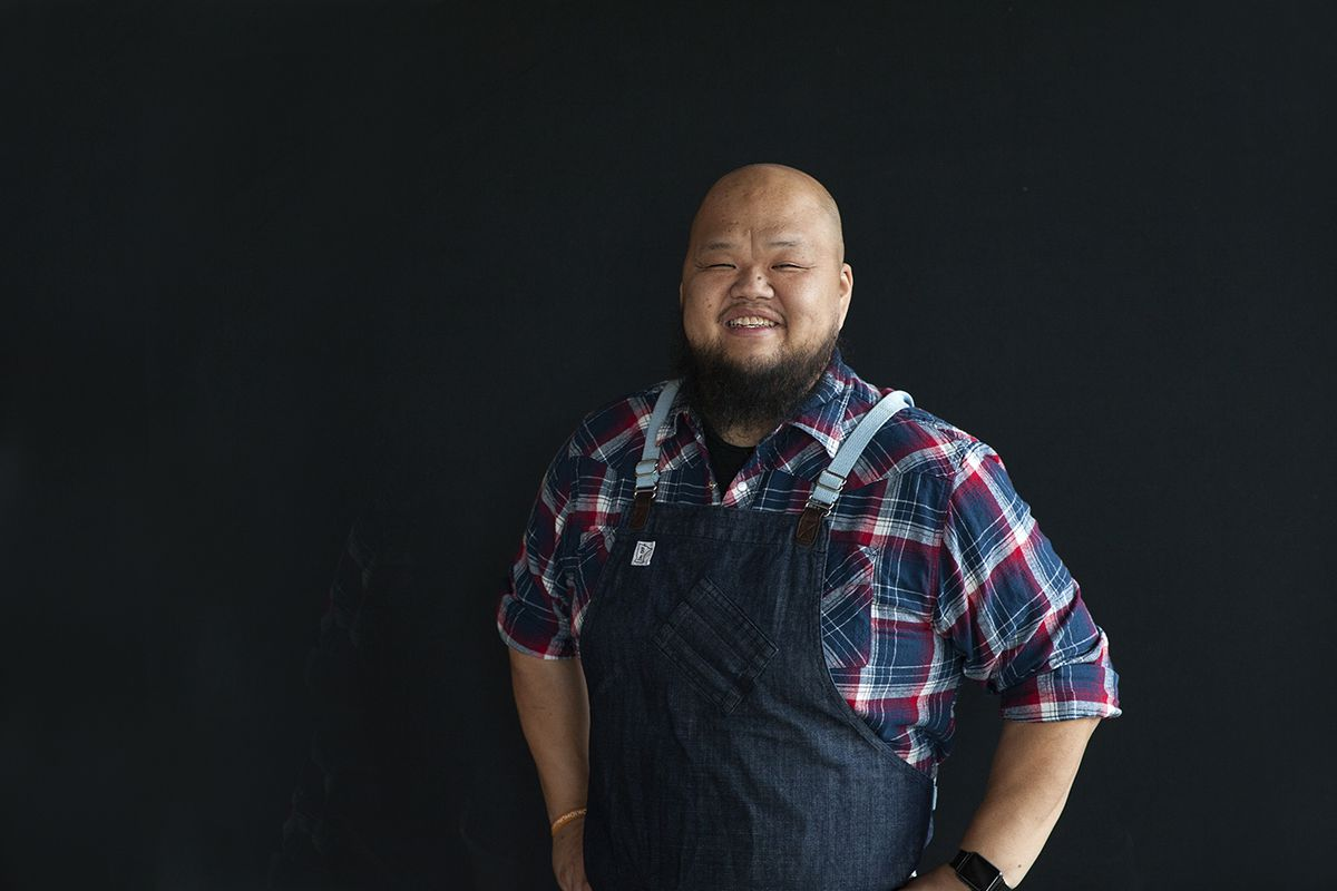 Chef Yia Vang is wearing a plaid shirt and denim apron, smiling, in front of a black background