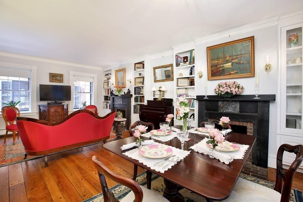 A dining area with a table and chairs next to the living room, and there are two fireplaces side by side.