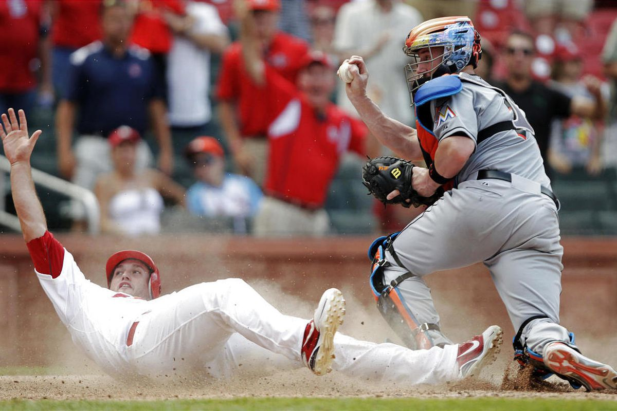 St. Louis Cardinals' David Freese (23) looks for the call as Miami Marlins catcher John Buck shows the ball in the ninth inning of a baseball game, Sunday, July 8, 2012, in St. Louis. Freese scored from second on a single by Rafael Furcal as the Cardinals