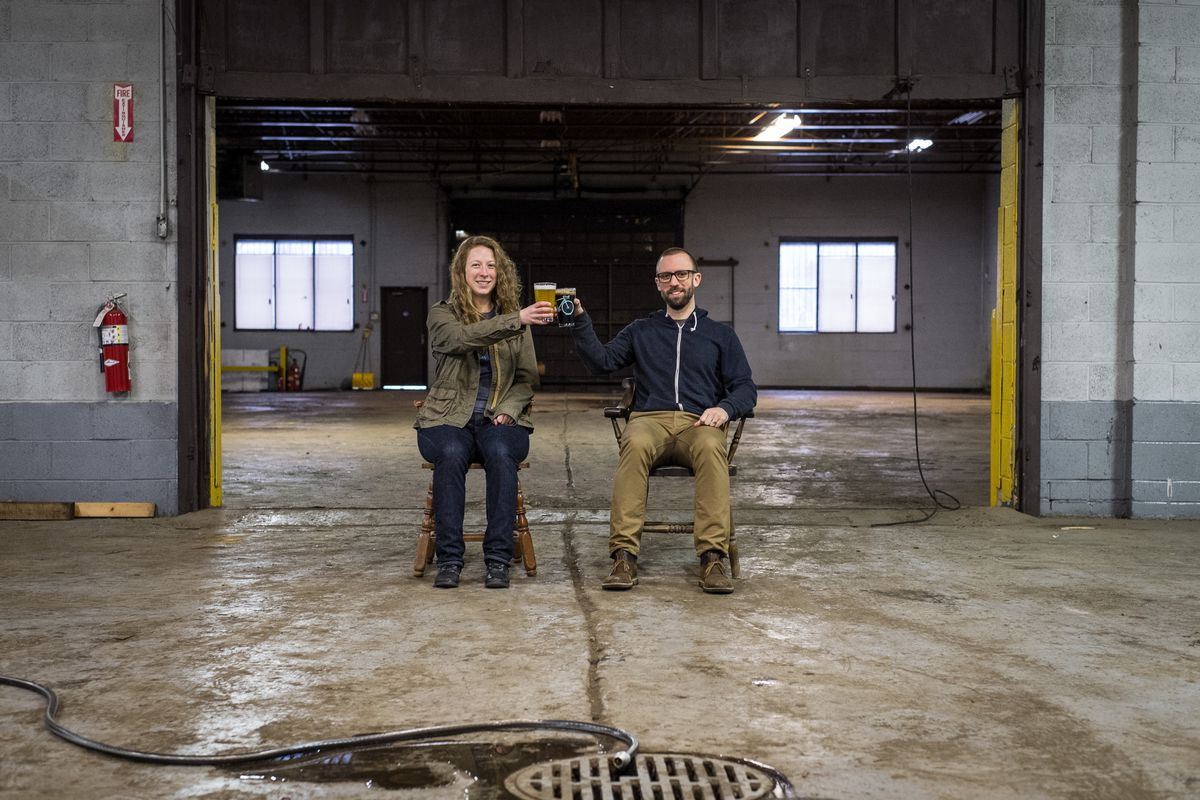 Rachel Szlaga and Paul Szlaga sit on chairs in their unfinished brewery warehouse cheersing with pints of beer.