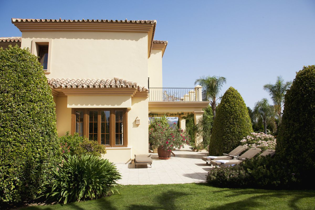 A Spanish-style home with green yard and large patio.