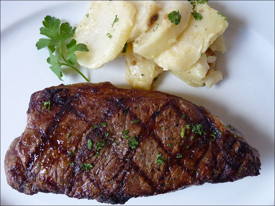 A steak garnished with parsley with mashed potatoes in the background