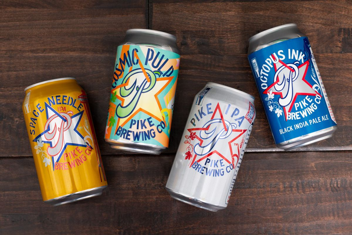 A selection of beer cans from Pike Brewing Co., from left to right, Space Needle, Cosmic Pulp, Pike IPA, and Octopus Ink, against a wood background