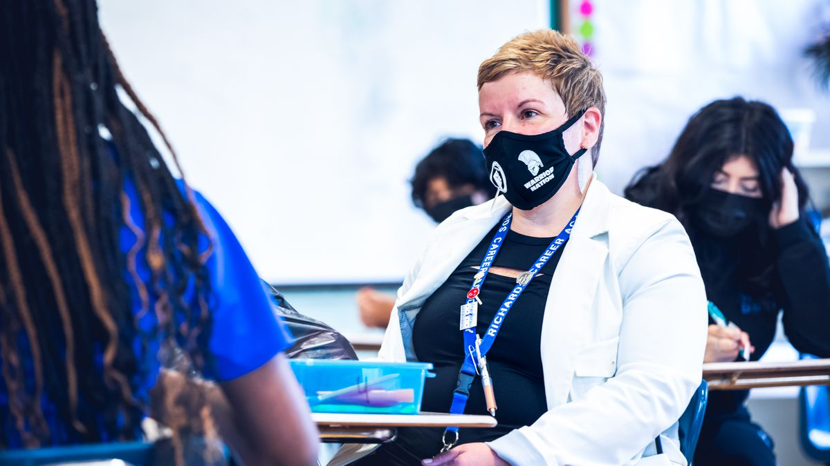 A woman in a face mask sits at a desk and speaks with a girl in a school classroom.