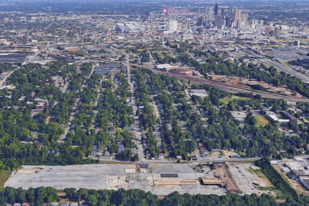 A large paved expanse, surrounded by trees and neighborhoods.