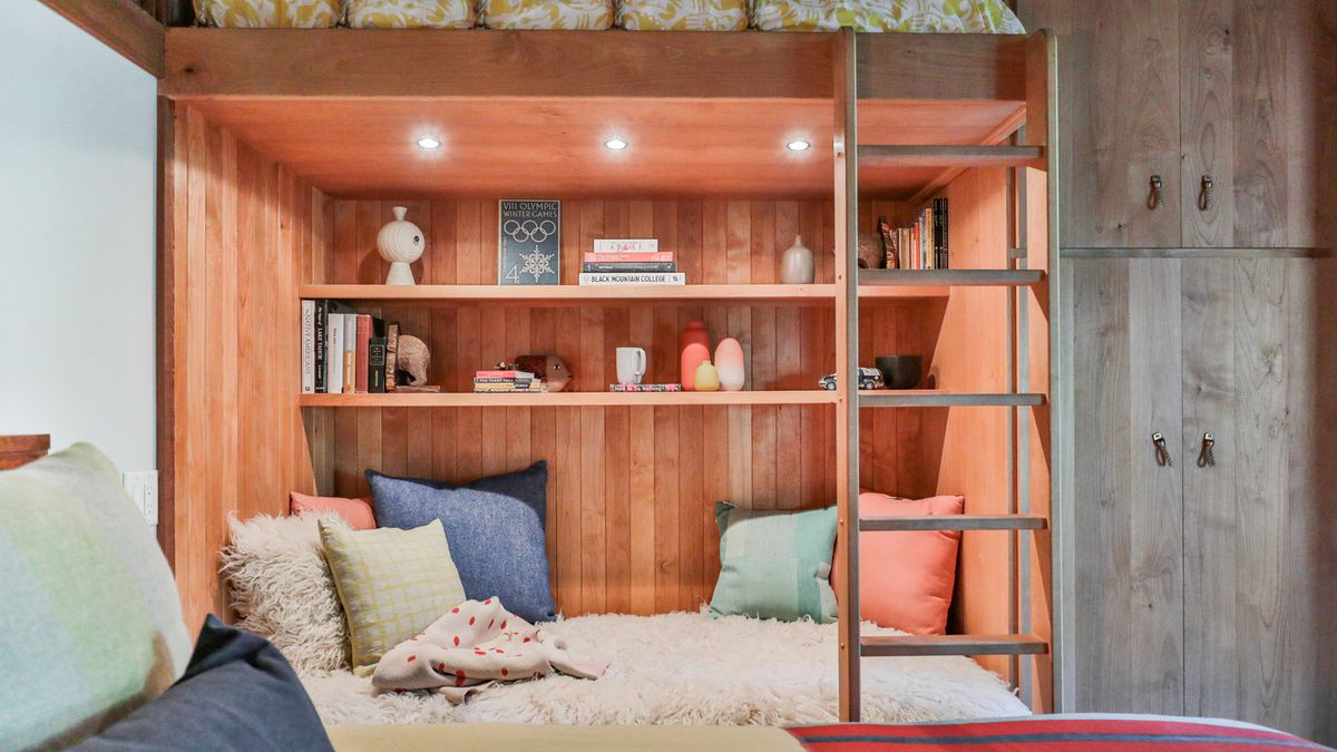 Wooden bookshelves with lights, books, and a few small ceramic vases.