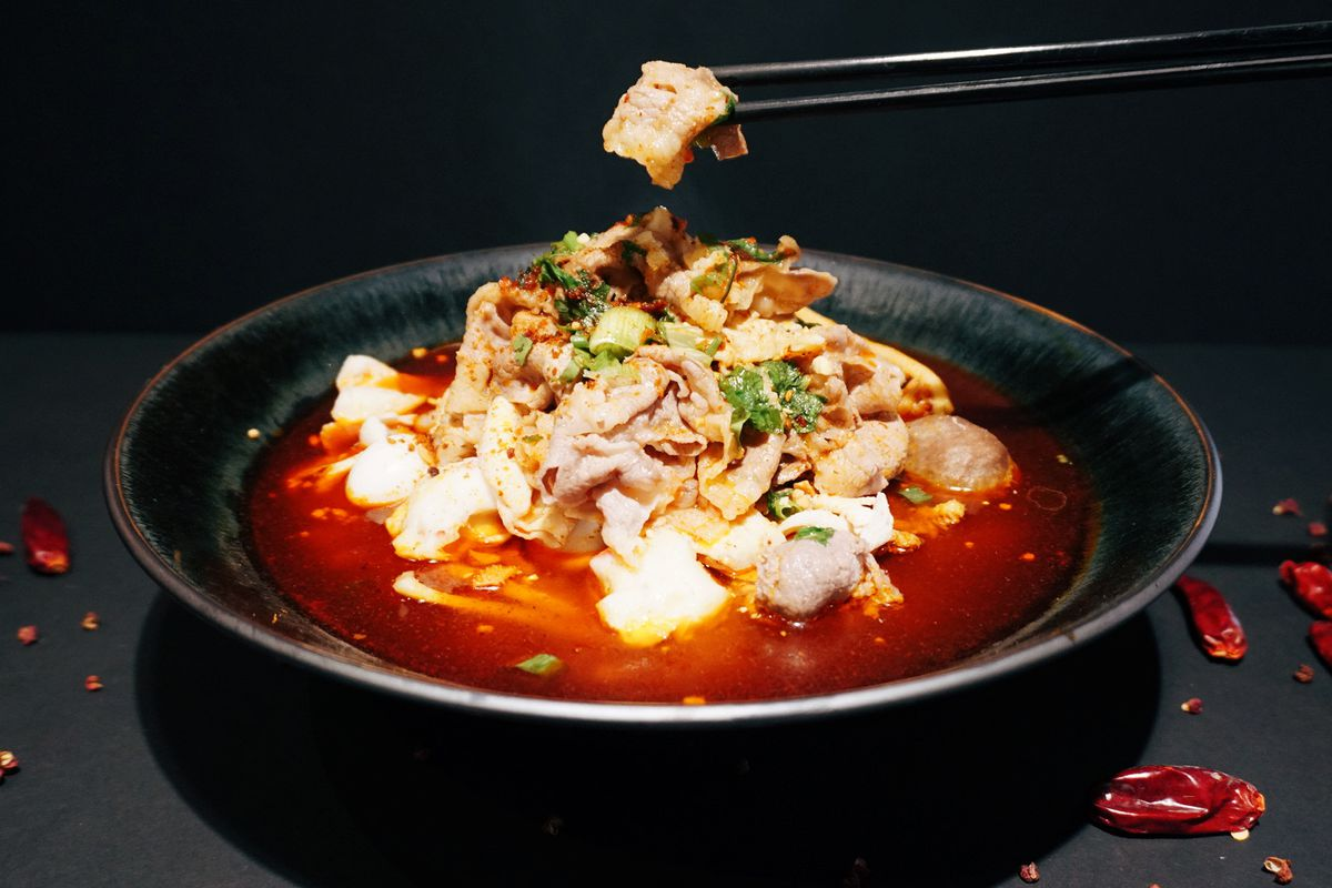 A black bowl with bright red broth and chopsticks lifting a thin piece of pork.