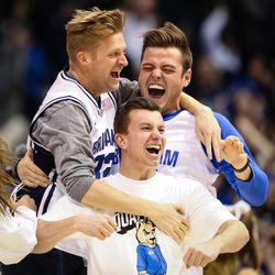 Christopher McLeod, center, reacts after he sinks a half-court shot to win $18,000 during the game between the BYU Cougars and the Saint Mary's Gaels in the Marriott Center in Provo on Saturday, Dec. 30, 2017.