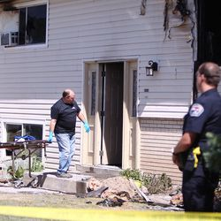 Medical examiners wheel a stretcher into a burned out house in West Valley City on Monday, June 5, 2017. A woman was found dead following the early morning blaze.